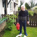 Service User watering flowers as part of the gardening project